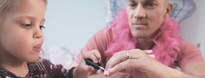 Father wearing a pink feather boa and letting his young daughter paint his fingernails pink