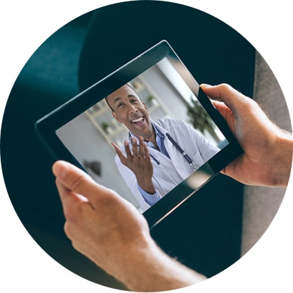 A man's hands holding a tablet device where he is having a virtual office visit with his doctor