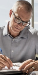Man in a dress shirt and eyeglasses making notes with a pen in an organizer binder