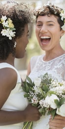 Smiling bride laughing with her maid of honor who holds a bouquet of white tulips