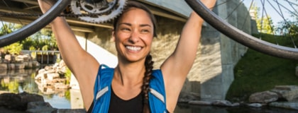 Smiling athletic woman holding her bicycle in the air to hook it onto a bike hanger