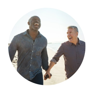 Image of two men holding hands laughing on the beach