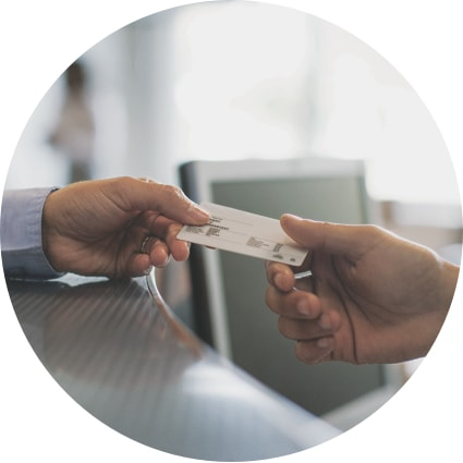 Man's hand giving his membership indentification care to a receptionist's hand