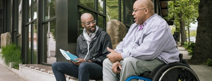 Bald man in a wheelchair talking animatedly to his male friend who is sitting on a bench next to him