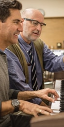 A mature man in eyeglasses teaches another man how to play piano