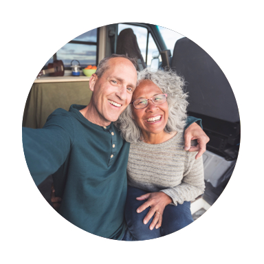 A smiling, balding man and a smiling woman with mid-length gray hear squeezing together to take a sitting selfie