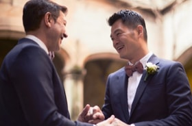 Two smiling men grasping hands in a church ceremony