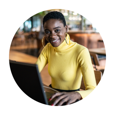 Image of woman smiling, working on laptop and sitting in a coffee shop