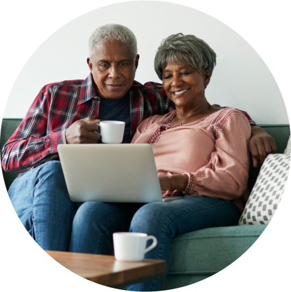 Elderly couple sitting together on the couch looking at laptop
