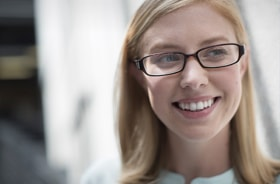 Face of a smiling blonde woman wearing eyeglasses